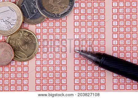 pen and bingo lotto lottery ticket with euro money and numbers.
