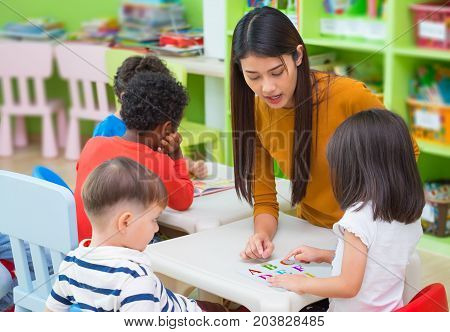 Asian female teacher teaching mixed race kids reading book in classroomKindergarten pre school concept.