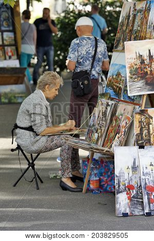 KARLOVY VARY, CZECH REPUBLIC - AUGUST 14: In the streets you can find a lot of folk artists with diffrent types of painting from landscape portraits to cartoons in Carlsbad Czech republic on August 14 2017