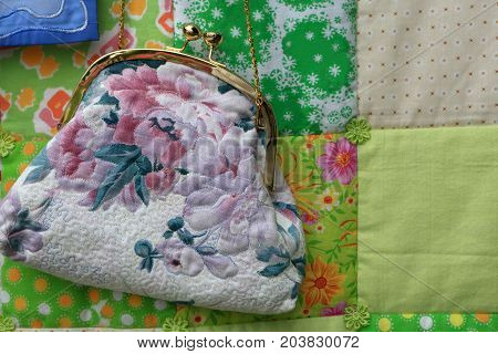Handbag with floral ornament on a carpet background