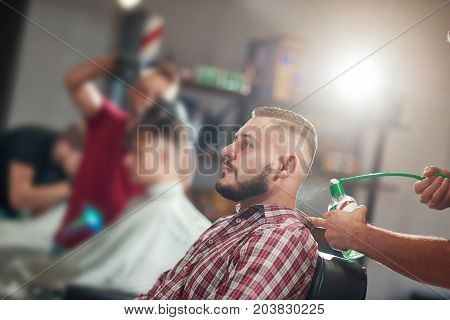 Shot of a bearded handsome young man at the barbershop. Professional barber spraying cologne at his client.