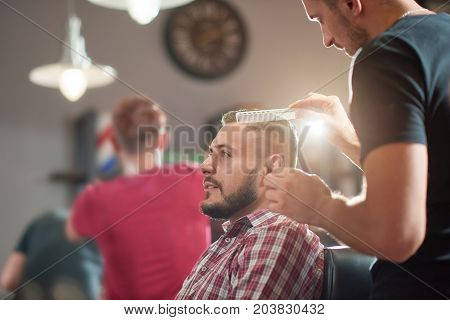Attractive young man relaxing sitting at the barbershop while getting his hair styled.