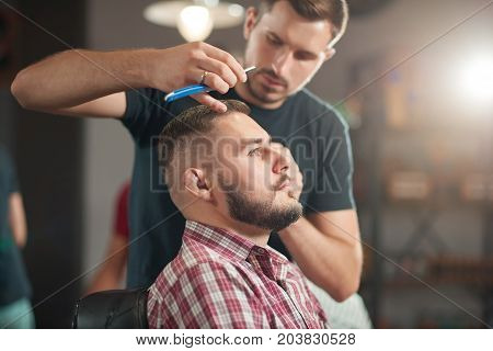Handsome young man getting a new hairstyle at the local barbershop.