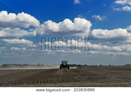Modern green tractor cultivating a field with deep blue sky and clouds on the background