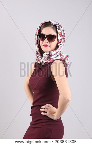 Pretty young woman in sunglasses dress and shawl poses in grey studio