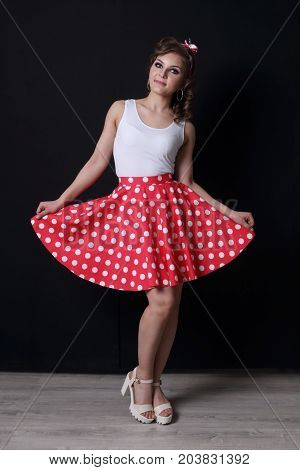Pinup beautiful girl in red skirt and with curly hair poses in black studio