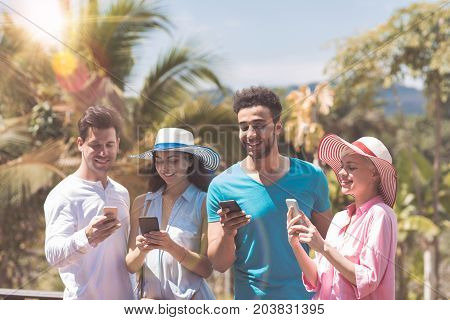 Happy Group Of Young People Messaging With Cell Smart Phones Outdoors On Summer Terrace With Tropical Forest View Mix Race Men And Women Social Media Communication Concept