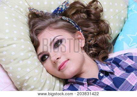 Pinup pretty girl in checkered shirt is on soft pillows in studio
