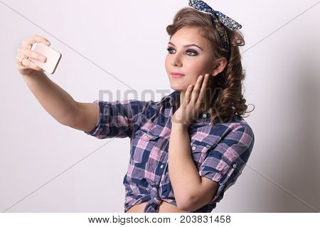 Pinup pretty girl in checkered shirt makes selfie by smartphone in studio
