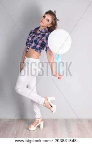 Pinup girl in checkered shirt and pants poses with balloon in studio