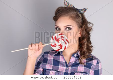 Pinup pretty girl in checkered shirt poses with lollipop in studio