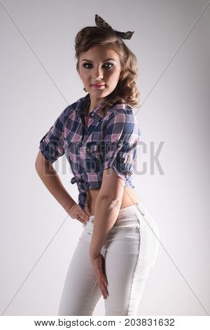Pinup beautiful woman in checkered shirt and with curly hair poses in studio