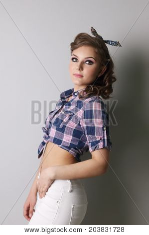 Pinup woman in checkered shirt and pants poses in grey studio