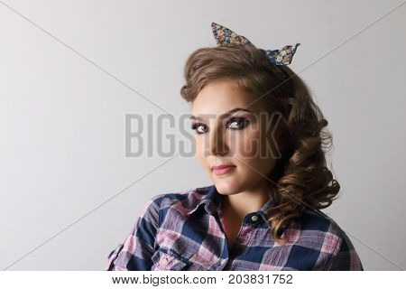 Pinup beautiful woman in checkered shirt and with bow in studio