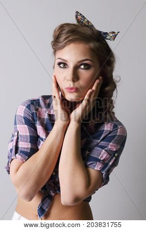 Pinup beautiful woman in checkered shirt kisses in grey studio