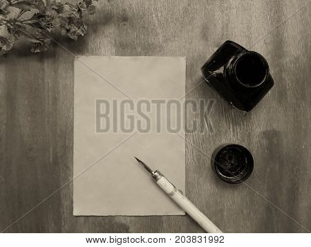 Dry autumn flowers and a blank old sheet of paper with a dip pen and an inkwell on a worn wooden background (view from the top or flat lay) retro style in sepia