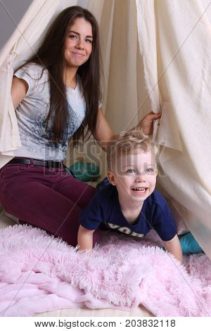 Mother and her little cute son play in wigwam with pillows at home focus on kid