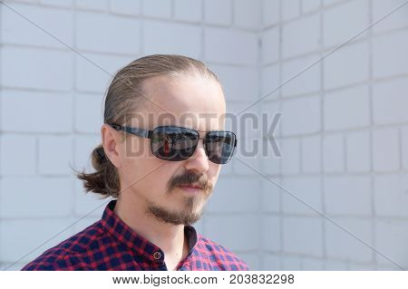 Looking away man portrait. Cheerful bearded hipster man in black glasses. Fashion stylish young men