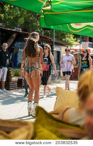 Hot Girl In Bikini Swimwear Drives Roller Skate. Back View