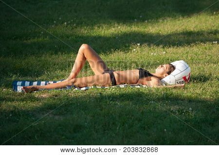 Beautiful Girl Is Sunbathing On The Grass In The Park