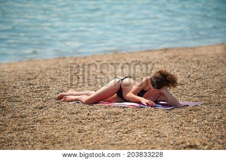 Beautiful Girl Reads The Book While Sunbathing On The Beach