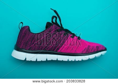 Pink And Black Sport Woman Shoes Isolated On Turquoise Background.