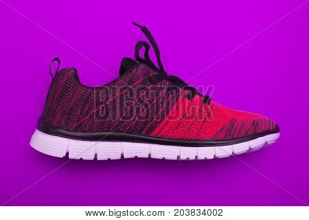 Red And Black Sport Woman Shoes Isolated On Purple Background.