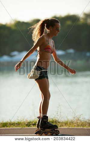 Girl In Bikini Swimwear And Jeans Shorts Drives Roller Skate