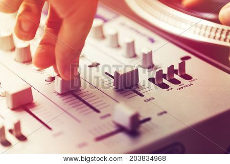 dj playing and mixing music on turntable controller