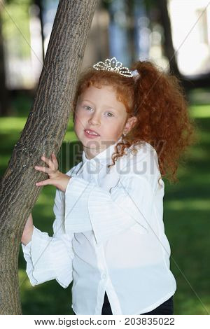 Little girl with red hair in diadem poses near tree in summer green park