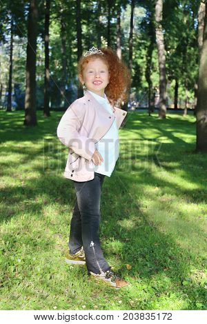 Happy little girl with red hair in diadem poses in summer green park at sunny day
