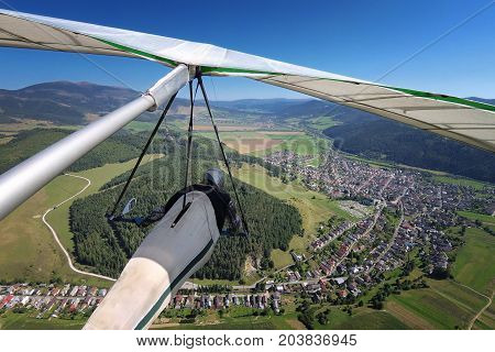 Hangglider pilot flies over small alpine town in mountain valley onboard shot with action camera.