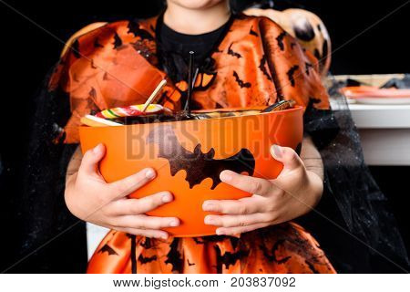 cropped view of child in witch costume of witch holding bowl full of halloween sweets isolated on black