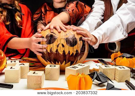 cropped view of kids with halloween jack pumpkin and aphabet blocks isolated on black