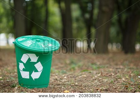 Green recycle bin isolated on earthen background with different rubbish and dry yellow leaves. Concept of envirometal protection. Uncultivated outside terrain.