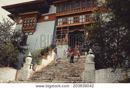 Paro, Bhutan - September 10, 2016: Low Angle View Of Tourists Standing On An Old Temple Stairs.