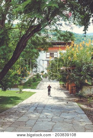 Paro, Bhutan - September 10, 2016: Man Walking On Bhutanese Temple Walkway On A Sunny Day.