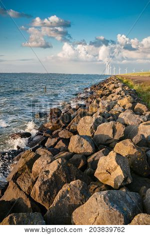 An inner lake in the Netherlands with waves striking on the stone dykes of the polder during sunset