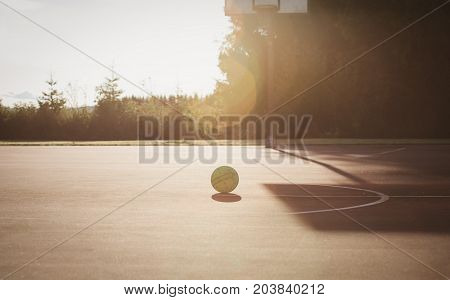 basketball playground and ball at sunset, ready to play