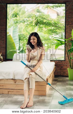 Woman Cleaning Floor With Mop Indoors. Relax After Doing Housework.