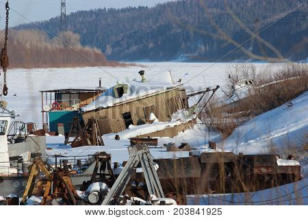 The Frozen River Port. Cranes, Barges, Old Buildings.