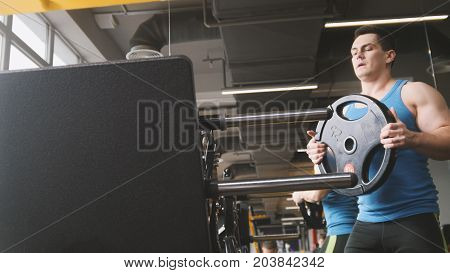Muscular sporty man add weight for squats machine in the gym, close up view