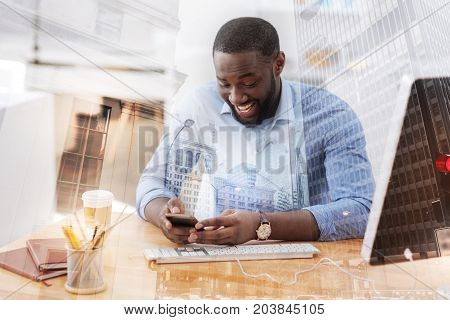 Fantastic photos. Close up of young excited African American holding mobile phone and looking at photos while showing huge interest