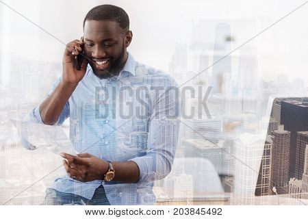 Sharing information. Waist up of young smiling man talking on the mobile phone while reading information from the document with enthusiasm
