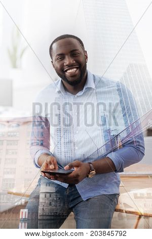 Having rest. Waist up of young delighted African American standing in front of you while using mobile phone and expressing positive emotions