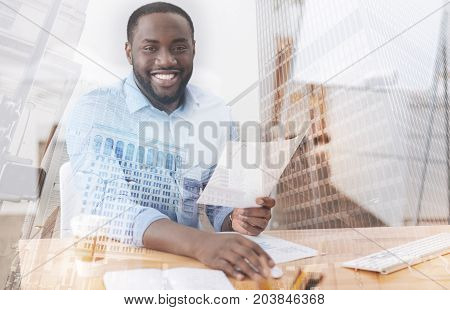 Being attentive. Close up of pleasant delighted employee sitting at the table while expressing excitement and happiness
