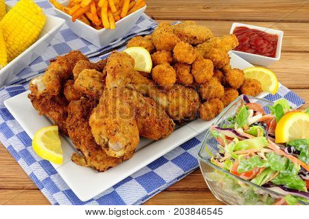 Collection of Southern fried chicken products with sweetcorn and salad