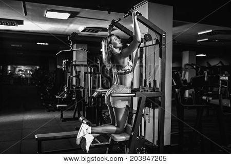 girl doing pull ups on simulator in gym