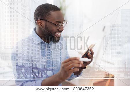 Always preparing. Close up of smart pleasant student holding a mobile phone while looking at the screen and expressing delight