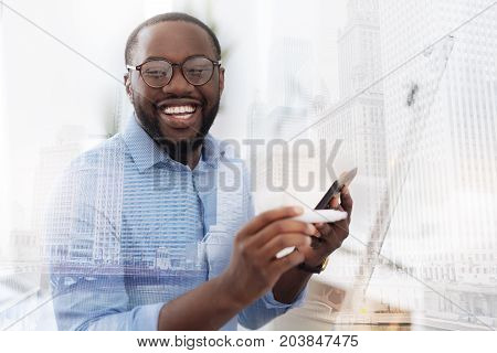 Feeling happy. Close up of young African American with glasses looking at you while holding a mobile phone in the hand